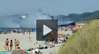 Un vaixell militar rus atraca en una platja plena de banyistes